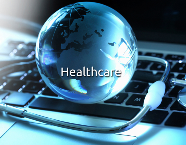 Glass globe and stethoscope on a keyboard signifying healthcare energy analytics.