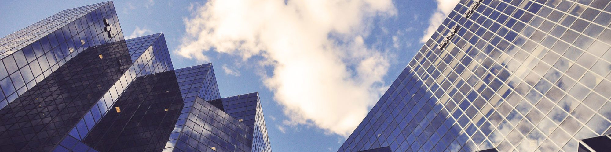 Office building in front of a cloudy blue sky.